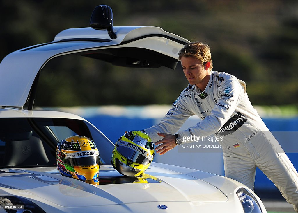 Mercedes' German driver Nico Rosberg drops his helmet on a car during a training session at the Jerez de la Frontera racetrack on February 4, 2013.