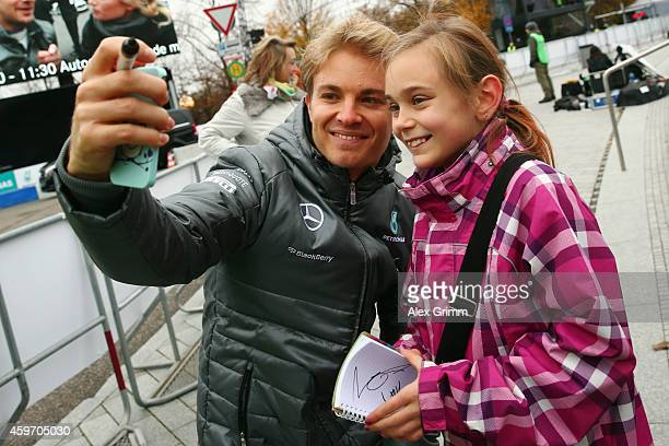 Mercedes GP Formula One driver Nico Rosberg of Germany shoots a selfie with a young fan during the annual Mercedes Benz Stars Cars event in front of...