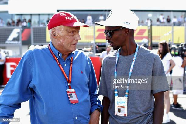 Mercedes GP nonexecutive chairman Niki Lauda talks with long distance running legend Sir Mo Farah on the grid before the Formula One Grand Prix of...