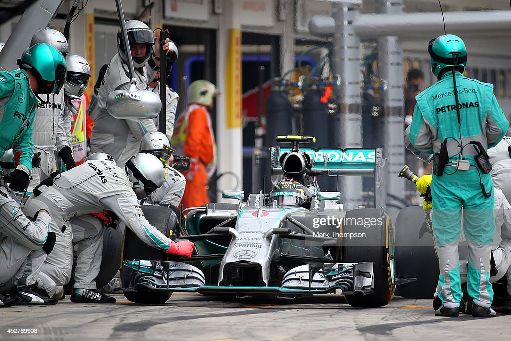 A Mercedes mechanic makes an adjustment to <a gi-track='captionPersonalityLinkClicked' href=/galleries/search?phrase=Nico+Rosberg&family=editorial&specificpeople=800808 ng-click='$event.stopPropagation()'>Nico Rosberg</a> of Germany and Mercedes GP's car after he has been released from a pit stop during the Hungarian Formula One Grand Prix at Hungaroring on July 27, 2014 in Budapest, Hungary.