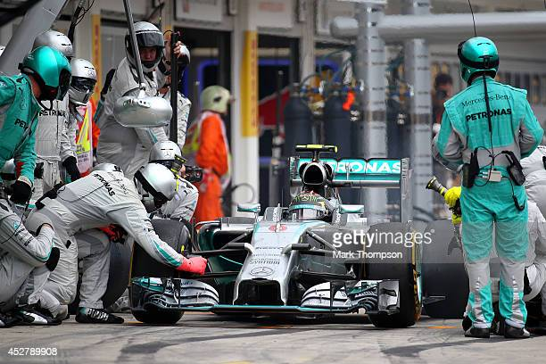 Mercedes mechanic makes an adjustment to Nico Rosberg of Germany and Mercedes GP's car after he has been released from a pit stop during the...