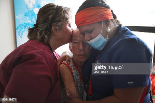Mercedes Perez is comforted by Sandra Alvarez MD and Brenda Francisco RN from the First Medical Relief team as they give her aide at the Pedro...
