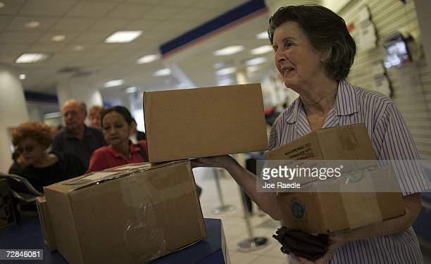 Mercedes Prats waits in line to mail Christmas gifts at a post office December 18 2006 in Coral Gables Florida According to the United States Postal...