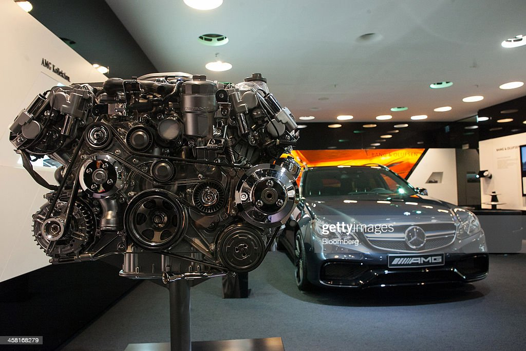 A Mercedes-AMG GmbH V8 engine stands on display beside a Mercedes-Benz AMG E63 automobile, produced by Daimler AG, inside the company's showroom in Berlin, Germany, on Thursday, Dec. 19, 2013. European new-car sales rose a third consecutive month in November, the longest period of gains in four years. Photographer: Krisztian Bocsi/Bloomberg via Getty Images