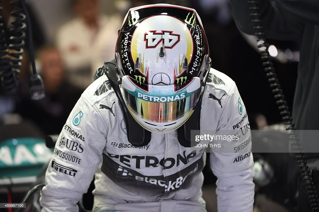Mercedes-AMG's British driver Lewis Hamilton hots into his car in the pits during the second practice session at the Spa-Francorchamps circuit in Spa on August 22, 2014 ahead of the Belgium Formula One Grand Prix.