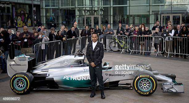 MercedesAMG's F1 driver Lewis Hamilton poses for pictures with a Mercedes F1 car during a photocall in Salford north west England on November 25 2014...