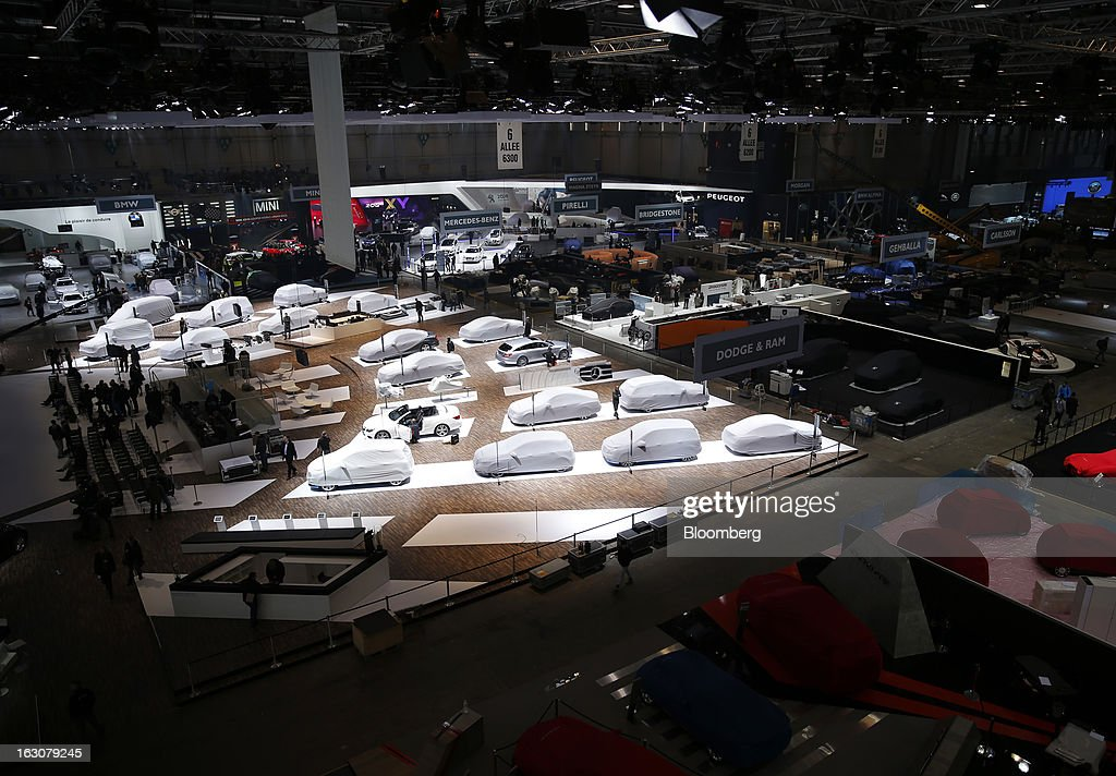 Mercedes-Benz automobiles, center, produced by Daimler AG, sit covered on the company's stand in an exhibition hall ahead of the opening day of the 83rd Geneva International Motor Show in Geneva, Switzerland, on Monday, March 4, 2013. This year's show opens to the public on Mar. 7, and is set to feature more than 100 product premiers from the world's automobile manufacturers. Photographer: Valentin Flauraud/Bloomberg via Getty Images