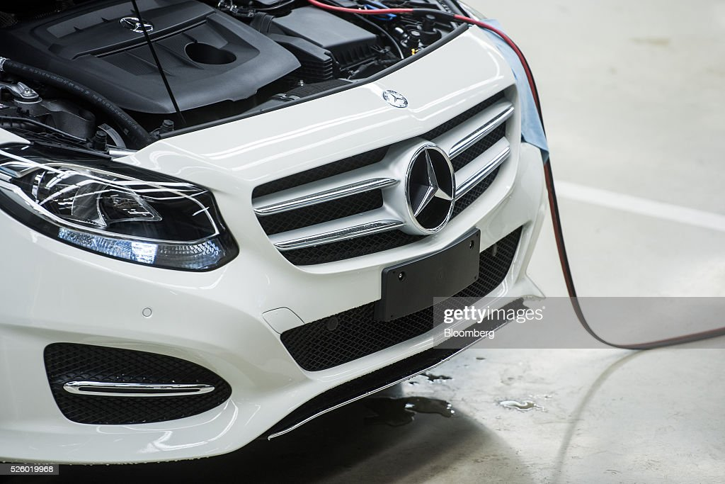 A Mercedes-Benz badge sits on the grill of an automobile beneath the open bonnet and engine at the Mercedes-Benz AG automobile plant, operated by Daimler AG, in Kecskemet, Hungary, on Friday, April 29, 2016. Daimler's Mercedes factory will produce a new generation of compact vehicles, totaling Daimler's investment in Hungary to more than $1.8 billion. Photographer: Akos Stiller/Bloomberg via Getty Images
