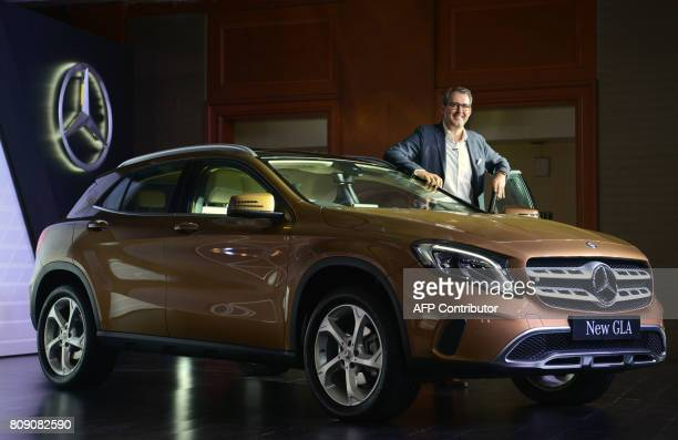 MercedesBenz India Vice President for Sales Michael Jopp poses for a photograph alongside a the new GLA series car during a launch event in Mumbai on...