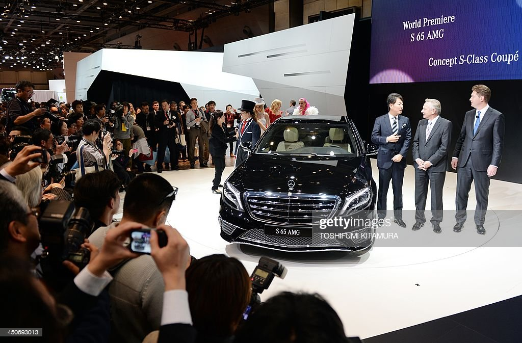 Mercedes-Benz officials (R) stand beside the company's 'S65 AMG' at a photo session during its world premier at the press briefing in the Tokyo Motor Show in Tokyo on November 20, 2013. The motor show, held from November 20 to December 1, features domestic makers of passenger cars, commercial vehicles and trucks alongside most of their European competitors.