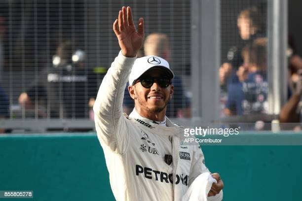 Mercedes's British driver Lewis Hamilton gestures after taking the pole position following the qualifying session of the Formula One Malaysia Grand...