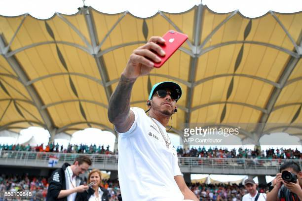 Mercedes's British driver Lewis Hamilton takes a selfie during the driver's parade before the start of the Formula One Malaysia Grand Prix in Sepang...