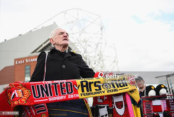 A merchandise seller holds the match scarf prior to the Barclays Premier League match between Manchester United and Arsenal at Old Trafford on...