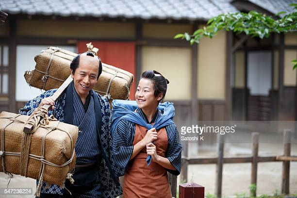 Merchant father and son walking together in old Edo village