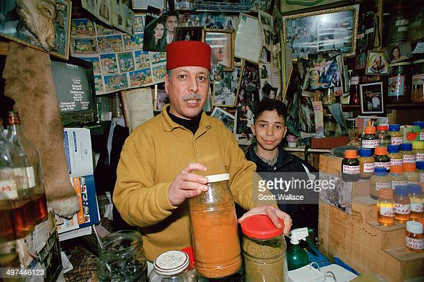 A merchant in the souq in Fes Morocco selling oils and spices 2004