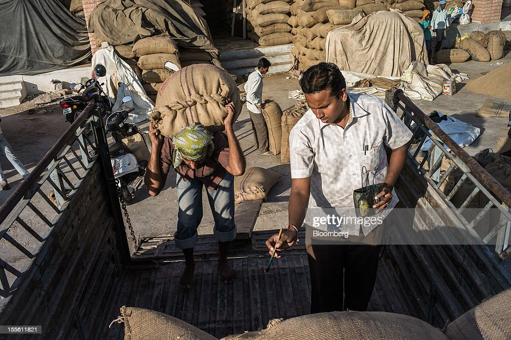 A merchant paints numbers on sacks of guar as a laborer loads them onto a truck at a grain market in Jodhpur, India, on Monday, Oct. 29, 2012. Guar gum is used to blend materials used in fracking. Photographer: Sanjit Das/Bloomberg via Getty Images