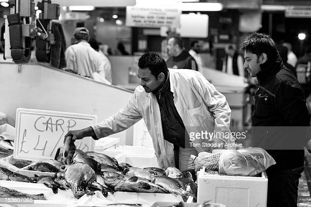 A merchant photographed with a customer at Billingsgate Fish Market near Canary Wharf in London's Docklands