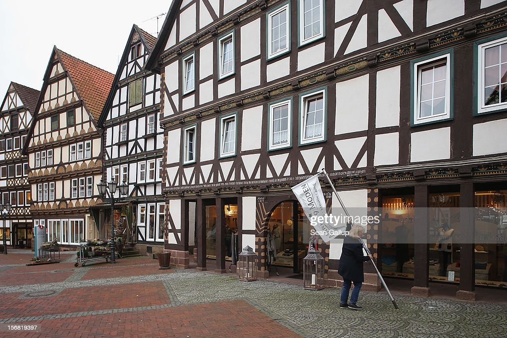 A merchant plants a banner outside her shop among half-timbered houses in a pedestrian street on November 19, 2012 in Hofgeismar, Germany. Hofgeismar lies along the 'Fairy Tale Road' (in German: Die Maerchenstrasse) that leads through the region between Frankfurt and Bremen where the Grimm brothers collected and adapted most of their fairy tales, which include such global classics as Sleeping Beauty, Little Red Riding Hood, Rapunzel, Cinderella and Hansel and Gretel, in the early 19th century. The 200th anniversary of the first publication of the stories will take place this coming December 20th.