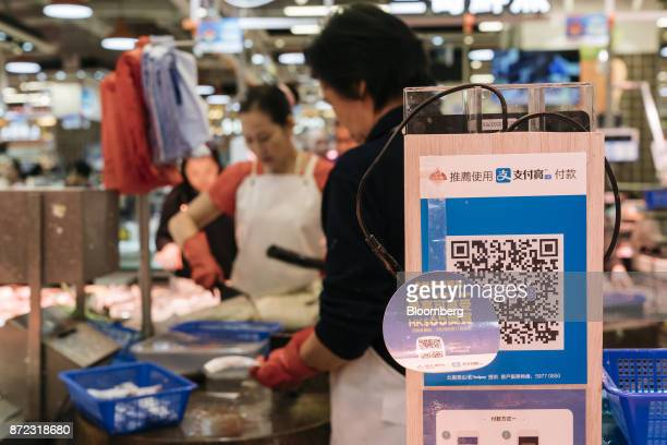 A merchant quick response code for Ant Financial Services Group's Alipay an affiliate of Alibaba Group Holding Ltd is displayed at a fish stall...