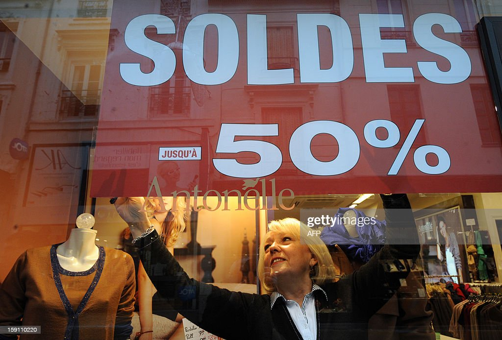 A merchant sets on a showcase an advertising banner announcing the sales on the eve of the start of the winter sales, on January 8, 2013 in Le Mans, western France.