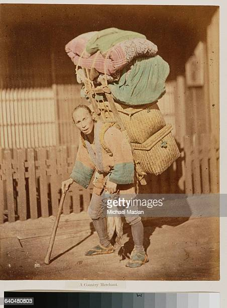 A merchant wearing regional attire carries two wicker baskets and several bundles of cloth using a wooden frame on his back He supports himself...