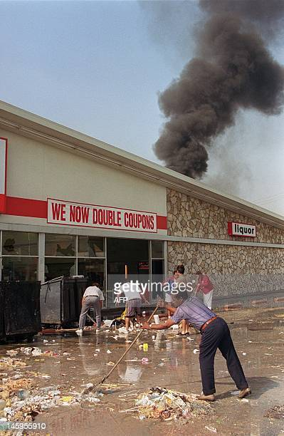 Merchants and volunteers clean up in front of a market that was burned and looted during riots 01 May 1992 in South Los Angeles The 1992 Los Angeles...
