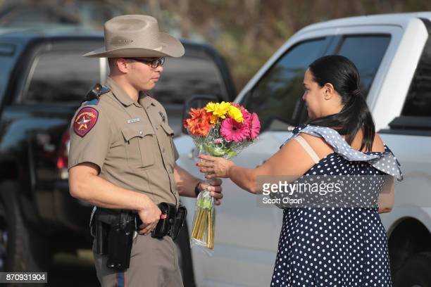 Meredeth Cooper hands flowers to a police officer guarding a road block near the First Baptist Church of Sutherland Springs on November 6 2017 in...