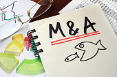 M&A Merger And Acquisitions written on a notepad with marker.