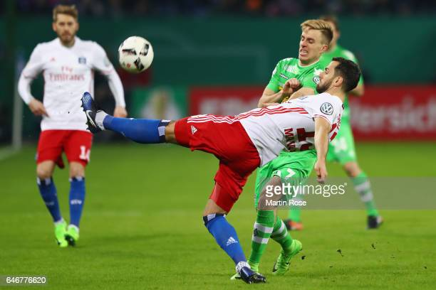 Mergim Mavraj of Hamburg is challenged by Patrick Herrmann of Moenchengladbach during the DFB Cup quarter final between Hamburger SV and Borussia...