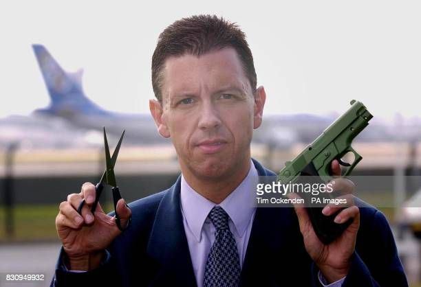 Meridian TV reporter Mike Pearse at Heathrow airport holding the replica gun and pair of scissors which were smuggled onto internal UK flights The...