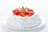 Meringue cake with fresh strawberry on white wooden background, close up view