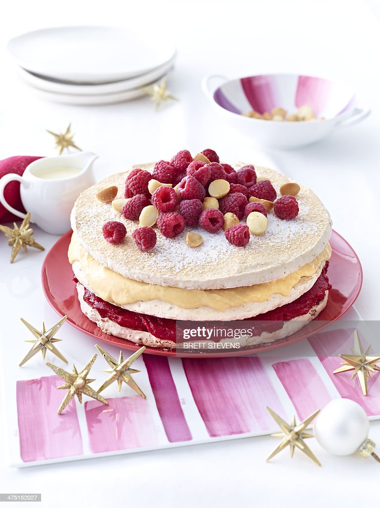 Meringue layer cake with raspberries and macadamia nuts : Stock Photo