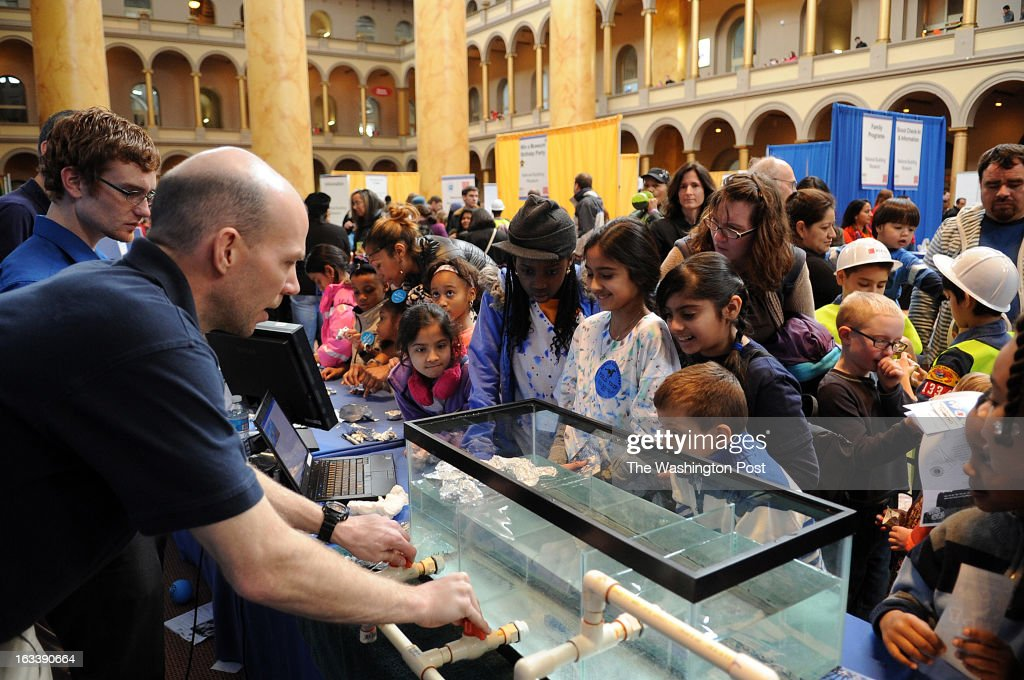 Meriyam Kapadia, 10, left, Stephanie Ajibola, 10, African American girl next to Meriyam, Isha Kaushal, 11, right from Stephanie, and Rithika Changal, 10, right, next to Isha, watch Jason Cawrse, who is a bridge ingeneer, operating a model of a locks system that explains how the extension of the Panama canal will work. The four girls built small boats of aluminum foil which are used to demonstrate how the canal locks system function. The girls are students of the Girls Excelling in Math and Science (GEMS), a club that started at McNair Elementary School in Herndon and is now in 30 Fairfax County schools and more outside the county, who take a field trip to the National Building Museum's Family Engineering Day.