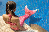 Mermaid girl with pink tail on rock at poolside put feet in water. Top view. Fun, vacation concept. Text space