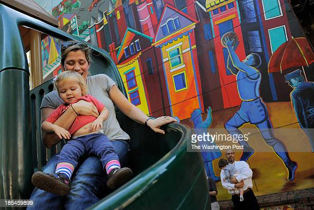 Merry Aldeman and her daughter Ginny Ritsch go down a slide in a neighborhood playground area along Westminster St NW on Monday October 14 2013 in...