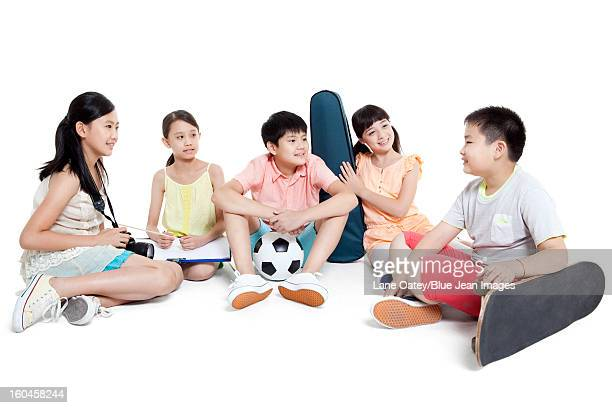 Merry children sitting on the floor and their leisure hobbies