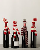 Merry Christmas and a Happy New Year! Bottles of wine in a knitted cap of Santa Claus. Selective focus.