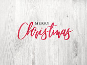 Festive Merry Christmas Calligraphy Text Over White Rustic Wood Background