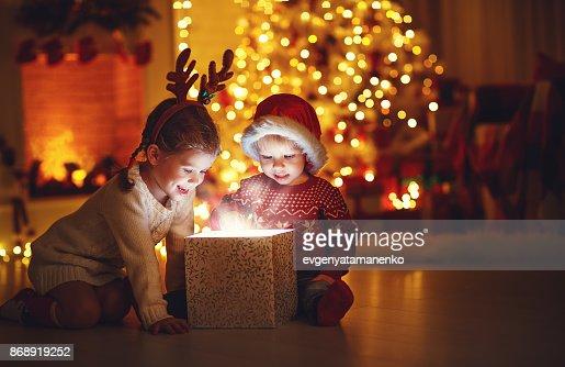 ¡Feliz Navidad! niños felices con un regalo mágico en casa : Foto de stock