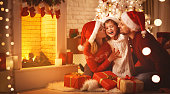 Merry Christmas! happy family mother father and child with magic gift near tree