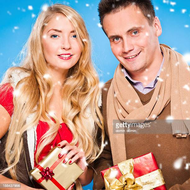 Merry Christmas, Happy young couple with gifts in hands smiling