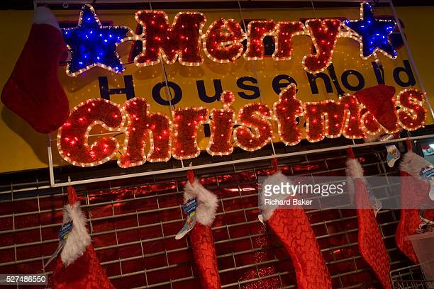 Merry Christmas lights and Chritmas stockings hanging up on shutters outside a shop in central London Attached to a neighbouring shop is the hanging...