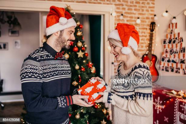 Merry Christmas. Man giving his girlfriend a present.
