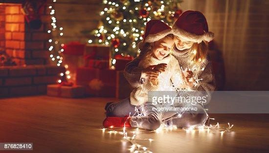 ¡Feliz Navidad! hija madre e hijo con guirnalda que brilla intensamente cerca de árbol : Foto de stock