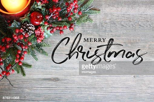 Texto de feliz Navidad, vela, ramas de pino y las bayas en la parte superior en madera rústica : Foto de stock