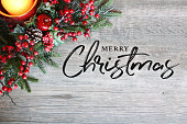 Merry Christmas Text, Festive Holiday Candle, Pine Tree Branches and Berries in Top Corner Over Rustic Wood Background