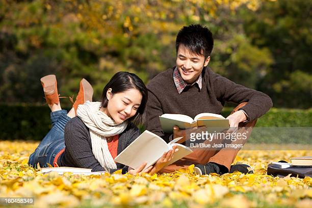 Merry college couple with books in the golden autumn on campus