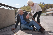 Genuine desire to help others. Old cheerful lovely man tripping over and spanking down while delicate woman raising this man
