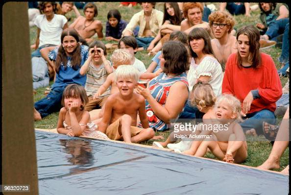 Merry Prankster and Hog Farmer kids watch puppet show at the Free Stage at the Woodstock music festival August 1969