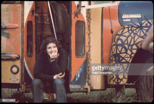 Merry Prankster girl sits in stairwell of handpainted bus at the Woodstock music festival August 1969